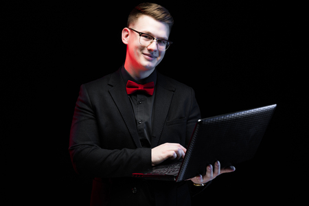 Young caucasian elegant successful smiling smart business man in black suit and red bow-tie standing in office with laptop looking in camera