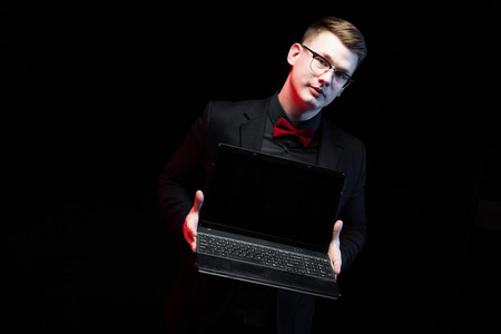Young caucasian elegant successful smiling smart business man in black suit and red bow-tie standing in office stretching out laptop looking in camera