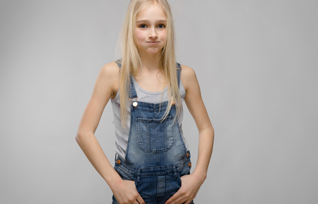 Portrait of beautiful teenage girl with blonde hair wearing denim overalls holding hands on pockets looking guilty isolated on grey background fashion advertising concept.