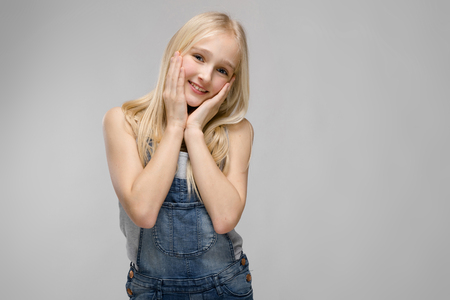 Portrait of beautiful cute teenage girl with blonde hair wearing denim overalls holding her hands on cheeks isolated on grey background fashion advertising concept. Stock Photo