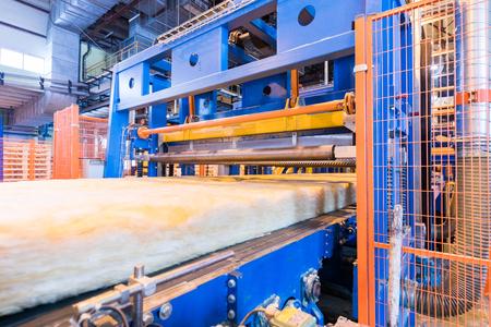 Modern operational plant equipment assembly line producing fiberglass batt heavy industry machinery metalworking workshop concept.