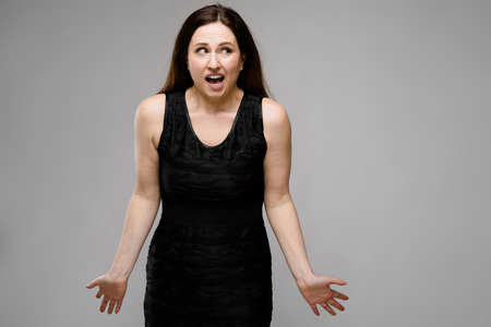 Half-length portrait of attractive happy serious brunette caucasian girl in black dress on gray background showing confuse despair bewilderment sign