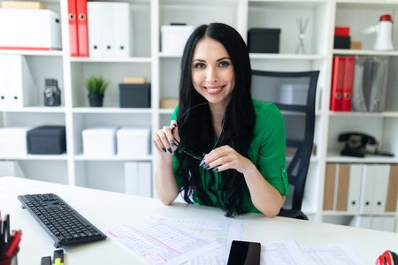 Beautiful girl in a green blouse and white pants sits at the office table. photo with depth of field.
