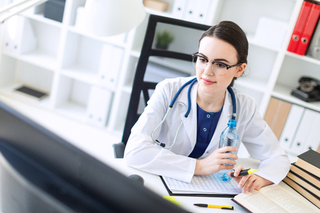 A charming young girl with glasses, a blue blouse and a white robe is sitting in the office. A stethoscope hangs around her neck. photo with depth of field. Imagens