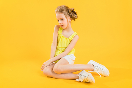Portrait of a girl in white shorts and a yellow topic.
