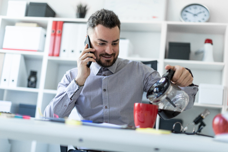 A bearded man in a light shirt and dark trousers is working in the office. photo with depth of field.