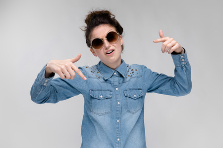Young girl in black cat glasses on a gray background. Charming girl in a blue denim shirt. Foto de archivo