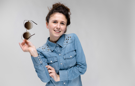 Young girl in black cat glasses on a gray background. Charming girl in a blue denim shirt. 写真素材