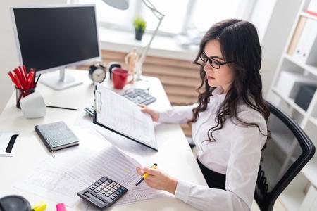 Een charmant jong meisje werkt in een helder kantoor. foto met scherptediepte. Stockfoto
