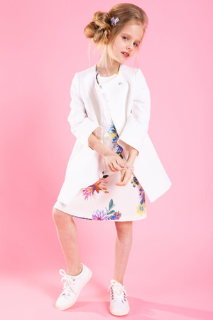 Portrait of a teenage girl in a white coat, a light dress in a flower and white sneakers.