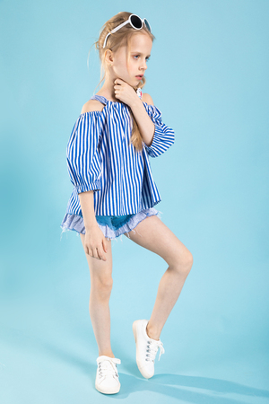 A teenage girl in a striped T-shirt, blue shorts and white sneakers posing on a light-blue background. Stockfoto