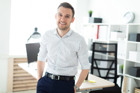 A young man in blue trousers and a light shirt. A handsome young man with a stubble on his face. photo with depth of field