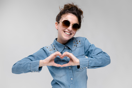 Young girl in black cat glasses on a gray background. Portrait of a young beautiful girl. Charming girl in a blue denim shirt. 写真素材
