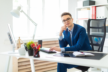 Casual businessman working in office, sitting at desk, typing on keyboard, looking at computer screen.