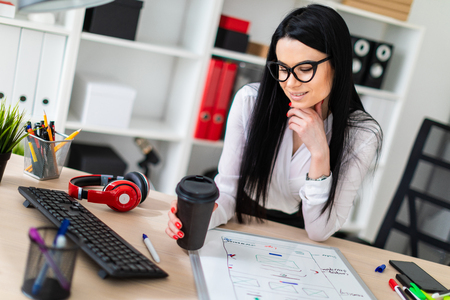 A young girl with glasses, wearing a white blouse and black trousers, works in the office. The girl has long straight black hair. photo with depth of field Stock Photo