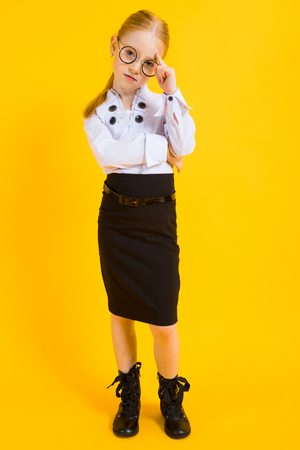 Portrait of a beautiful girl in a white blouse and a brown pencil skirt.