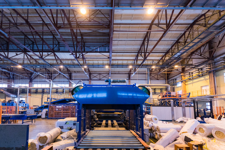Modern operational plant equipment producing fiberglass with rolls of rock wool or glass wool on the background heavy industry machinery metalworking workshop concept.