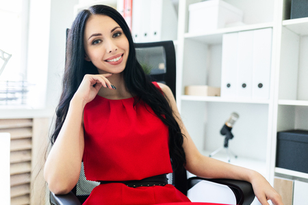 Portrait of a young girl in a red business suit.