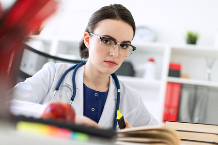 A charming young girl with glasses, a blue blouse and a white robe is sitting in the office. The girl has a stethoscope on her neck. photo with depth of field. Stock Photo