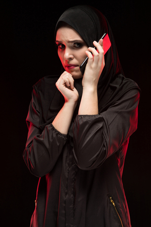 Attractive confident serious upset desperate muslim arabian woman dressed in black hijab standing in studio looking away bewildered holding mobile phone asking for help 免版税图像