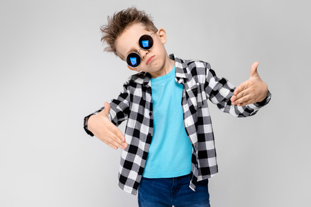 Charming happy child on gray background. The boys hair is up. The boy has a hairstyle. The boy in round sunglasses. A beautiful boy with a red hair color Imagens