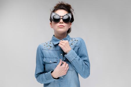 Young girl in black cat glasses on a gray background. Portrait of a young beautiful girl. Charming girl in a blue denim shirt. The girl is preparing for the exit.