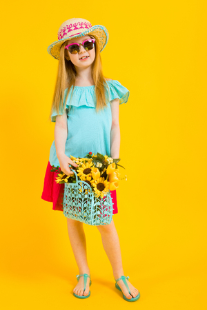 Portrait of a beautiful girl in a hat, sunglasses, summer dress and sandals.