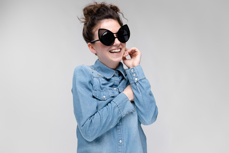 Young girl in black cat glasses on a gray background. Portrait of a young beautiful girl. Charming girl in a blue denim shirt. The girl is happy. 写真素材 - 103307910