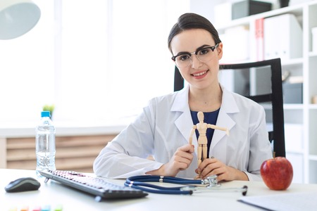 A charming young girl with glasses, a blue blouse and a white robe is sitting in the office. A stethoscope lies on the table in front of the girl. photo with depth of field. Stock Photo