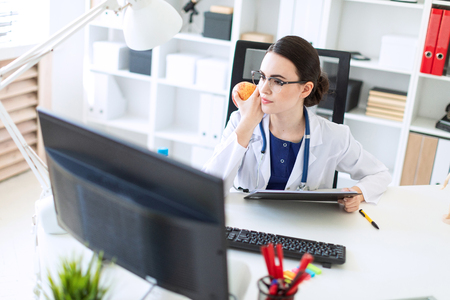 A charming young girl with glasses, a blue blouse and a white robe is sitting in the office. The girl in the bright office is working at the computer. photo with depth of field.