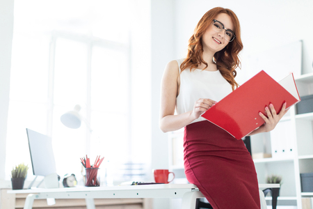 A red-haired young girl with glasses, a white blouse and a red skirt is working in the office. photo with depth of field