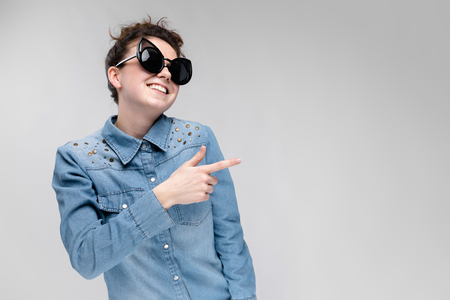 Young girl in black cat glasses on a gray background. Portrait of a young beautiful girl. Charming girl in a blue denim shirt. The girl has fun.