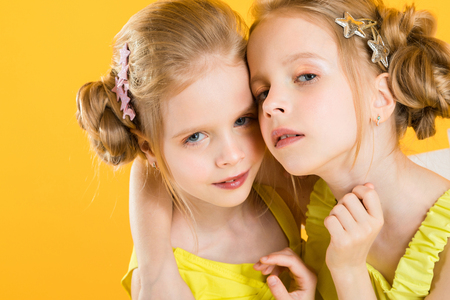 Twins girls in yellow clothes posing in the studio.