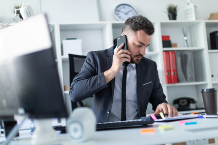 A bearded man with a business suit is working in a bright office. photo with depth of field.
