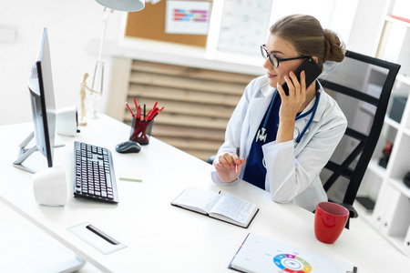A young girl in glasses and a white coat is working in her office. photo with depth of field Stock Photo