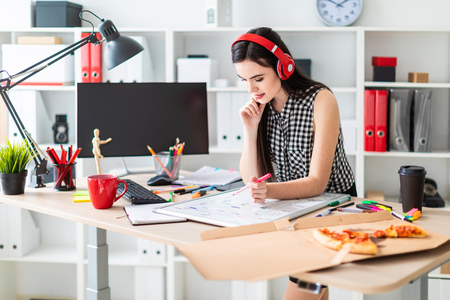 A beautiful girl in a black and white sleeveless shirt listens to music through red headphones and works with a marker and a magnetic board in a light cabinet. photo with depth of field Foto de archivo