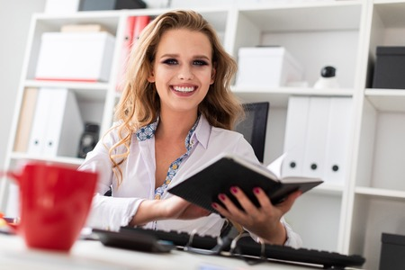 A young blond girl in a white blouse is working in the office. photo with depth of field.