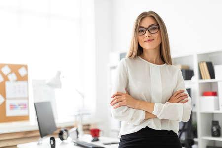 Schönes junges blondes Mädchen in der weißen Bluse und im schwarzen Rock arbeitet im Büro. Foto mit Schärfentiefe