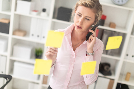 Beautiful young girl with blond hair in a pink blouse is working in the office. photo with depth of field