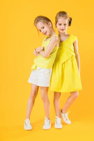 Des jumeaux drôles de filles s'amusent ensemble sur le fond jaune. Banque d'images