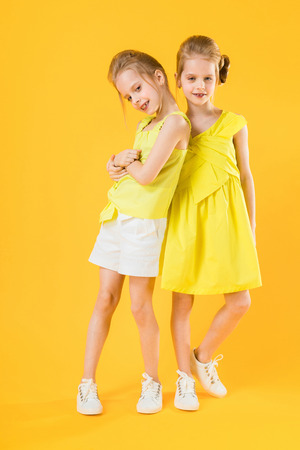 Las gemelas de chicas divertidas se divierten juntos en el fondo amarillo. Foto de archivo