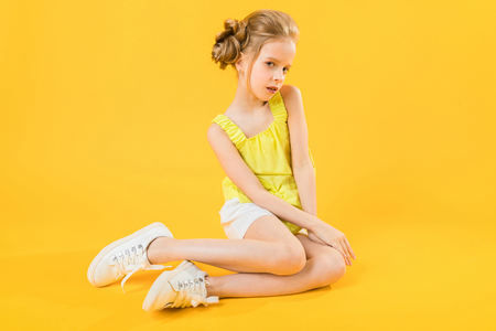 Portrait of a girl in white shorts and a yellow topic. Imagens