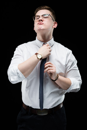 Young caucasian elegant smart business man in white shirt standing in office looking in camera waiting for a client holding his hand on tie Фото со стока