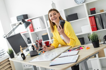 A beautiful young girl in a white T-shirt and a yellow jacket is working in a bright office. photo with depth of field Stock Photo