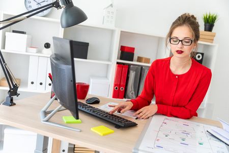 Beautiful young girl in glasses and a red shirt is working in the office. photo with depth of field.