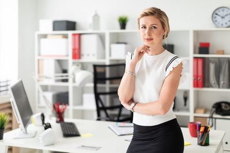 Beautiful young girl with blond hair in a white shirt is working in the office. photo with depth of field