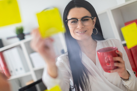 A young girl with glasses, wearing a white blouse and black trousers, works in the office. The girl has long straight black hair. photo with depth of field Stok Fotoğraf