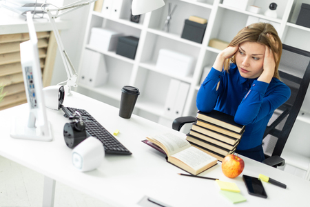 Beautiful young girl in a blue shirt is working in a bright office. photo with depth of field