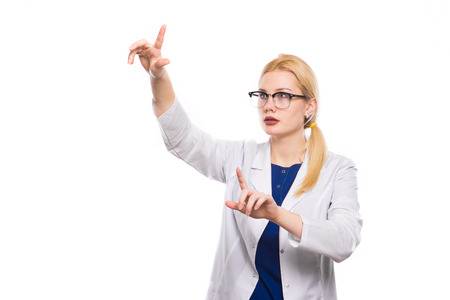 Portrait of intelligent thoughtful female doctor in white coat and glasses carefully examines someting in her hands isolated on white background with copyspace. Stock Photo