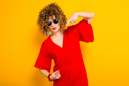Portrait of a white woman with afrro curly hairstyle in red dress and sunglasses pointing down isolated on orange background with copyspace beauty salon advertisement concept. Stock Photo